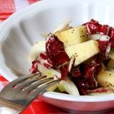 Insalata con radicchio e mela servita in ciotola bianca appoggiata su tovaglietta quadrettata bianca e rossa