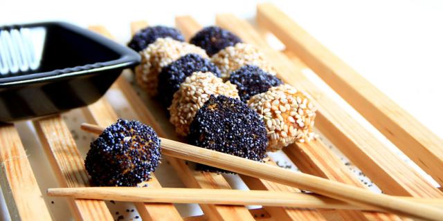 """Varie polpette vegetali """"impanate"""" di semi di lino e sesamo con a fianco due bacchette cinesi."""