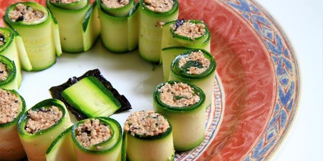 rotolini di zucchine con ripieno di semi e alghe dentro un piatto