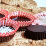 Quattro ciooccolatini di cacao e olio di cocco, tre dentro i pirottini di carta, uno sbucciato e riposto, su un centrino di canapa, capovolto.