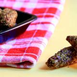 Grissini corti crudisti, fatti di semi di lino, zucchine e peperoncino, alcuni in una ciotola nera, due in primo piano disposti sul piano