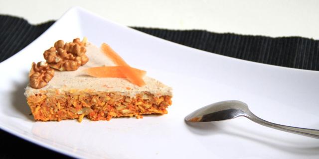 Una fetta di torta di carote e frutta secca su un piatto bianco accanto un cucchiaino