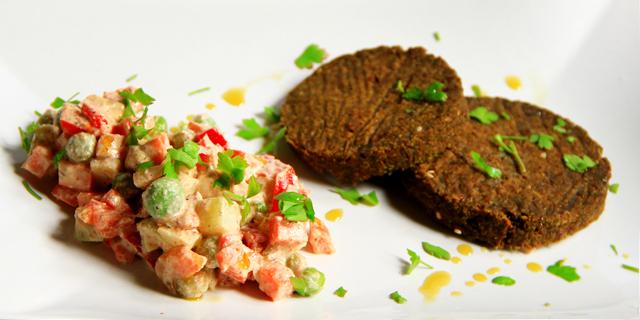 Insalata russa crudista accanto a due hamburger di carrube, semi e verdure, il tutto spolverato con del prezzemolo