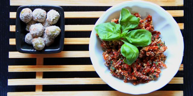 Una ciotolina nera che contiene olive ascolane crudiste e una ciotolina bianca che contiene pomodori secchi infarinati decorati con un grosso ciuffo di basilico
