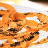 Piatto bianco con fette di zucca dal colore arancione condite con olio alle erbe