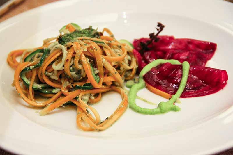 Spaghetti bicolore di zucchine e zucca conditi con pesto al basilico. Nello stesso piatto tre ravioli di barbabietola.