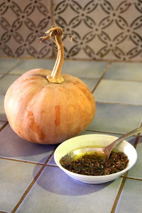 Una piccola zucca accanto ad una ciotolina bianca con olio e erbe aromatiche
