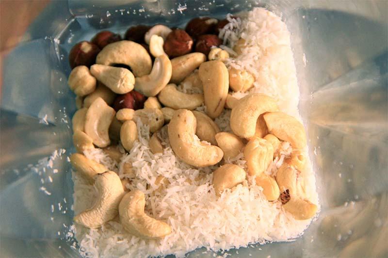 Dentro il frullatore si vedono anacardi, farina di cocco e nocciole.