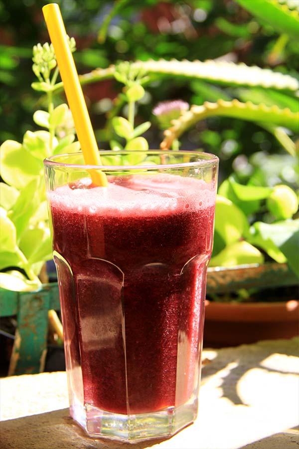 Bicchiere con succo d'uva nera illuminato dalla luce del sole con uno sfondo di fogliame