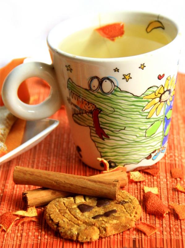 Biscotto e infuso arancia e cannella su una tovaglietta arancione cosparsa di bucce di arancia e rotoli di cannella