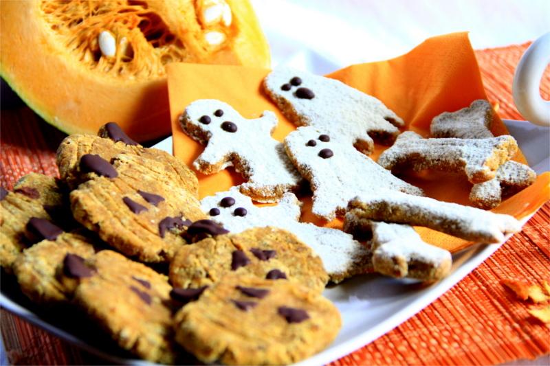 Biscotti zucca, fantasmini e ossa dentro un piatto , sullo sfondo mezza zucca