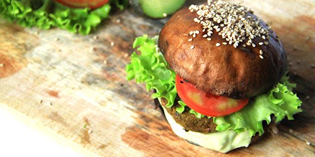 Burger di fungo con hamburger crudista, maionese crudista, pomodoro e lattuga, sopra un tagliere di legno.