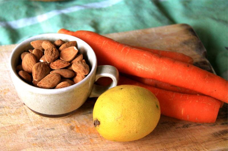 Mandorle, carote e limone adagiati su un tagliere