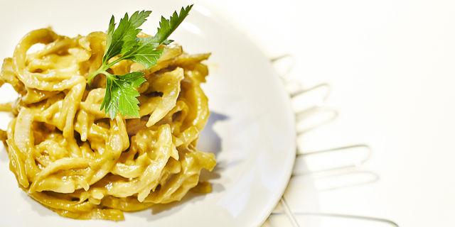 Spaghetti di daikon in salsa di avocado su un piatto bianco. Decorato con una foglia di prezzemolo.