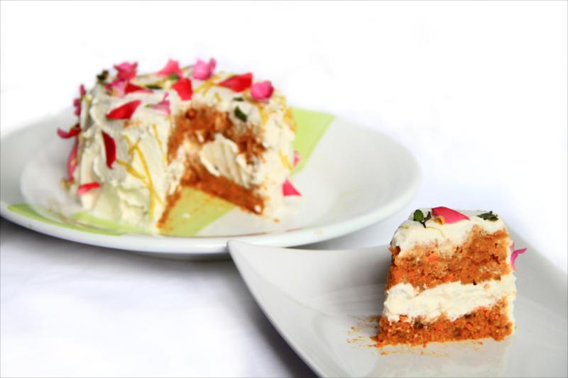 Una fetta di torta in primo piano. Sullo sfondo l'intera torta su un piatto