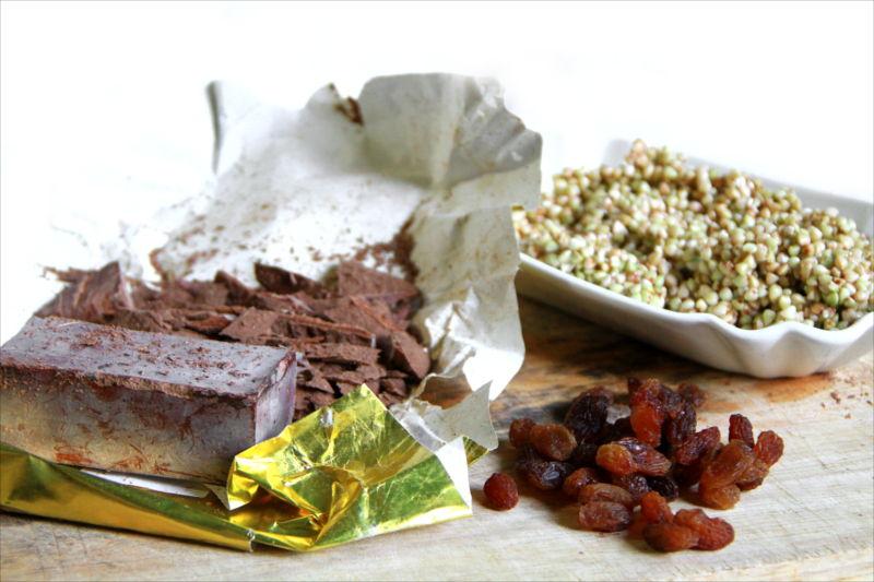 Pasta di cacao in scaglie, uvetta e grano saraceno in una terrina bianca, tutto adagiato su di un tagliere