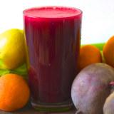Succo di barbabietola in un bicchiere insieme a frutta e barbabietole