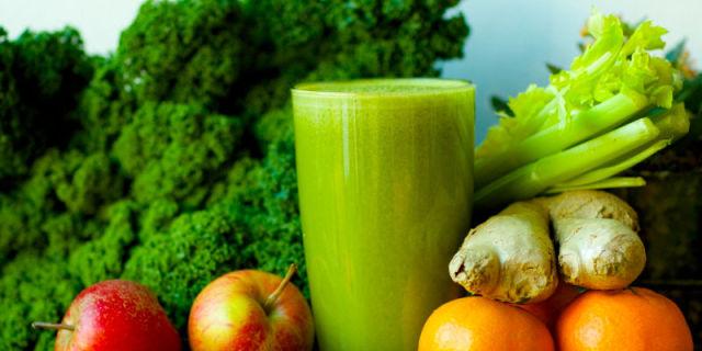 Bicchiere di succo verde in mezzo a frutta e verdura freschi