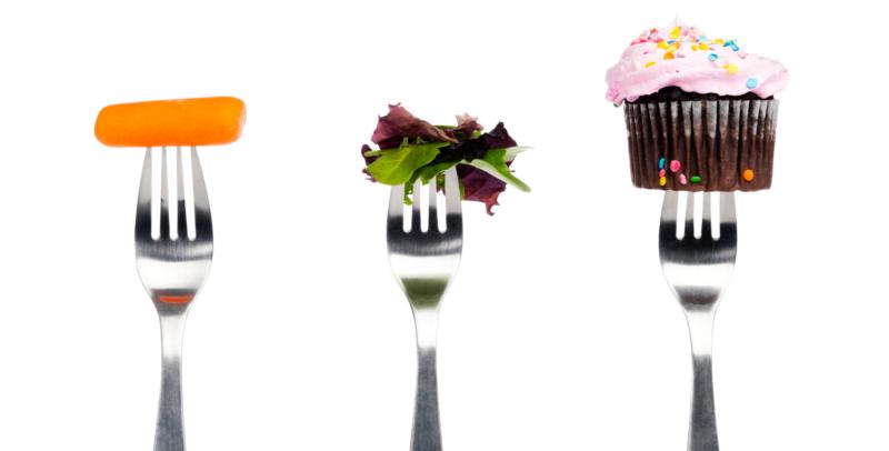 Tre forchette con tre cibi diversi, da sinistra una carota, dell'insalata e un muffin