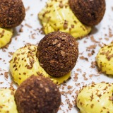 Palline di cioccolato e frutta adagiate accanto a palline di crema gialla di cocco