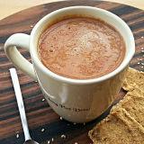 Cappuccino crudista all'interno di una tazza, accanto qualche biscotto crudista e del sesamo sparso