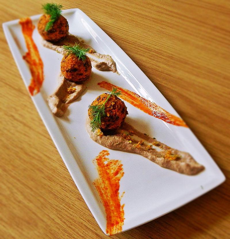 Tre polpette in fila su un piatto stretto e lungo. Decorato con salse e germogli di finocchio