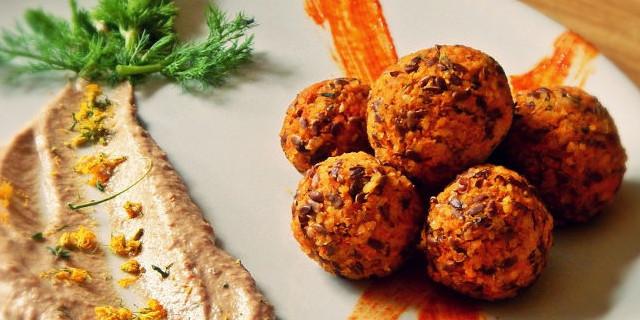 Polpettine crudiste disposte a stella su un piatto bianco, al di sotto due strisce di salsa arancione, accanto una cucchiaiata spalmata di salsa