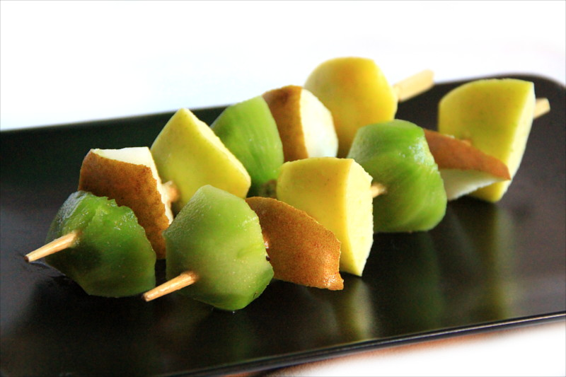 Spiedini di kiwi, pera e mela adagiati su un piatto nero