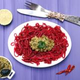 Un piatto bianco ovale contenente degli spaghetti crudisti di colore rosso, conditi con una salsa al centro. Sul piano una ciotola con altra salsa, tre peperoncini secchi, delle posate e mezzo limone. Il tavolo è di colore azzurro.