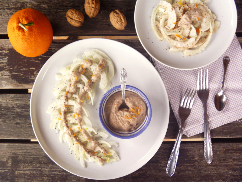 Un piatto con dei finocchi, al centro una ciotolina con crema di noci. Accanto al piatto tre forchette, un cucchiaino, un altro piatto con l'insalata e un'arancia e tre noci.