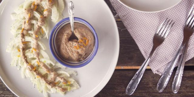 Un piatto con dei finocchi, al centro una ciotolina con crema di noci. Accanto al piatto tre forchette.