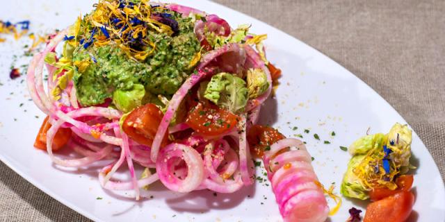 Spaghetti di rapa rossa conditi con pesto di cavolo nero, decorato con fiori colorati