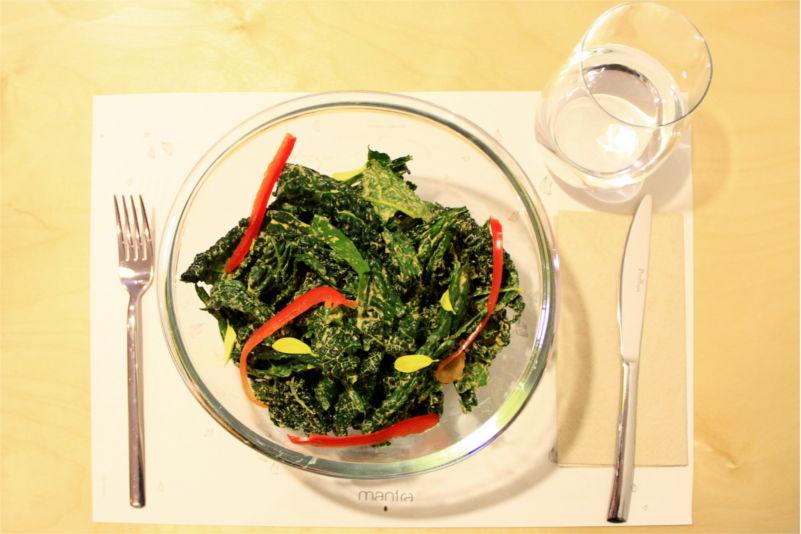 Una ciotola di vetro contenente un'insalata di cavolo nero al formaggio crudista, decorato da petali gialli e strisce di peperone rosso