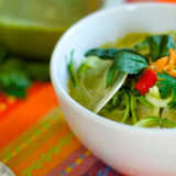 Una ciotolina bianca contenente una salsa verde e verdure miste