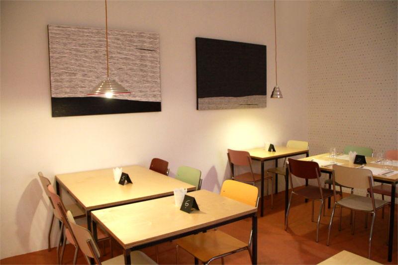 Interno del locale Mantra, tavoli in legno, sedie colorate, quadri alla parete