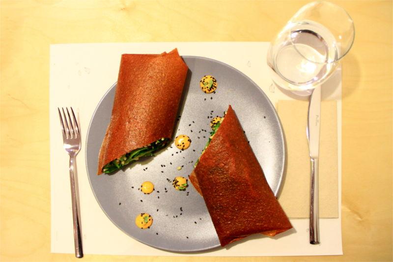 Involtino ripieno di verdure tagliato a metà e servito con palline di salsa al peperone