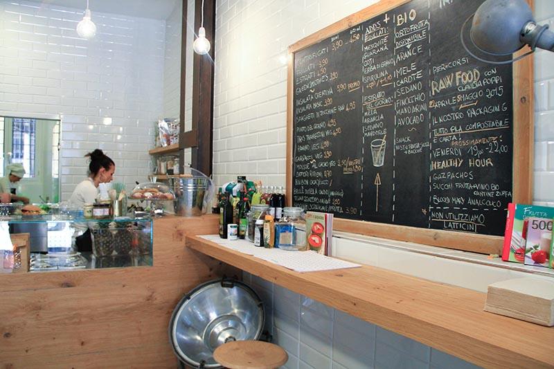 Interno Pistinega. Una lavagna a muro con tutto il menù e un bancone dove sedersi.