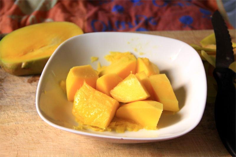 Pezzi di mango all'interno di un piatto bianco. Sullo sfondo il nocciolo interno del mango.