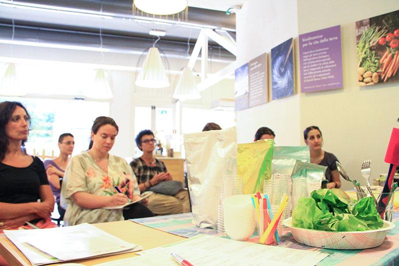 Inquadratura bassa, in primo piano tavola imbandita sullo sfondo alcuni partecipanti