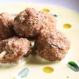 Polpette crudiste cavolfiore al centro di un piatto bianco, il tutto decorato da foglie di maggiorana e gocce di olio d'oliva