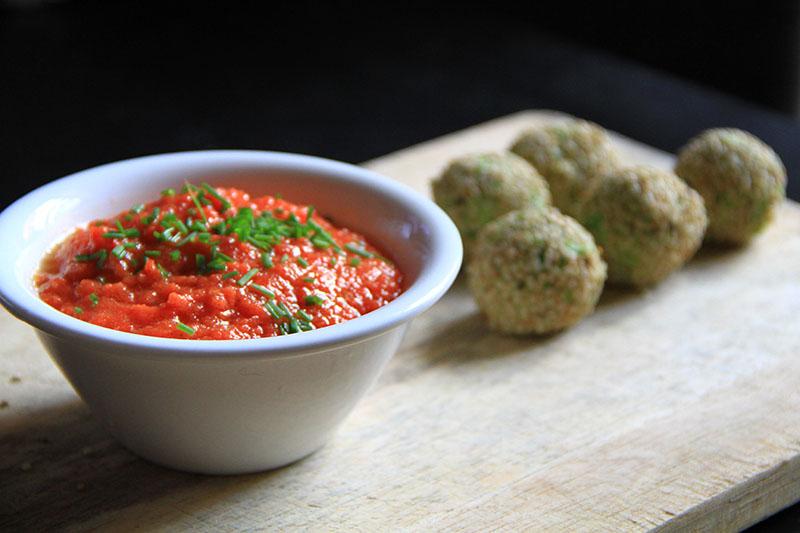 Una ciotolina bianca contente una salsa di pomodoro, accanto alcune polpette di piselli e noci.