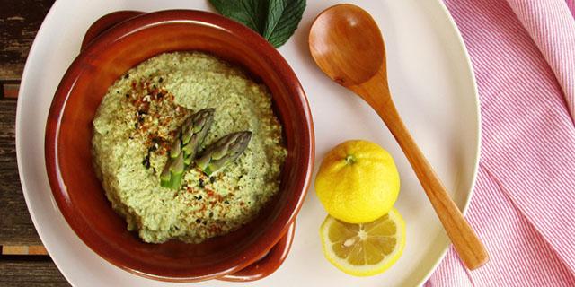 Una ciotola di coccio con all'interno una crema verde sormontata da due teste di asparago. Accanto un limone tagliato, due foglie di menta e un cucchiaio di legno.
