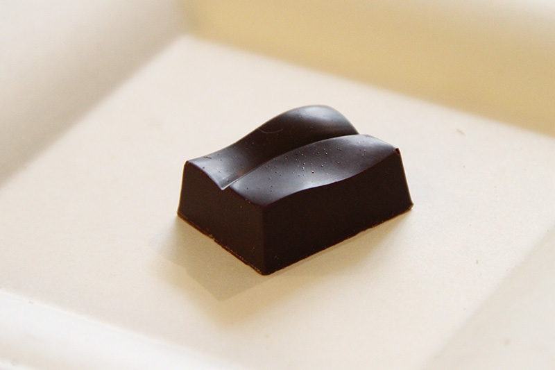 Cioccolatino crudista su sfondo neutro.
