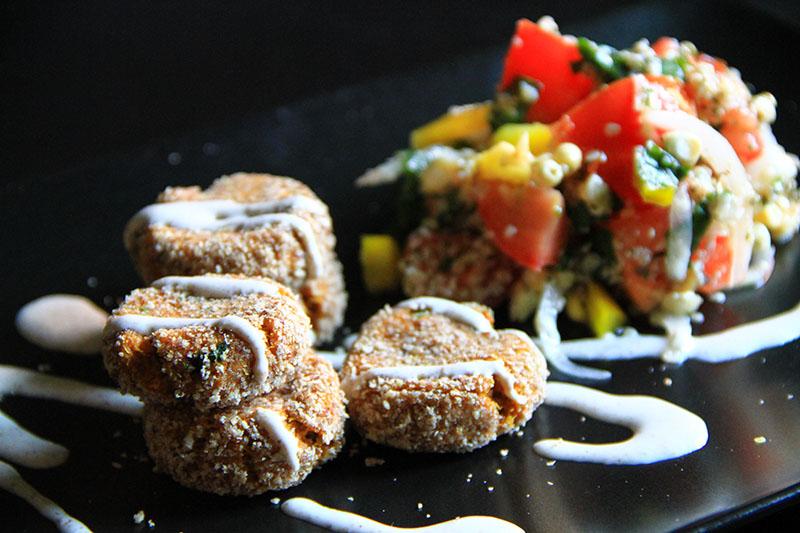 Falafel crudisti su piatto nero, accanto un tabbouleh e salsa allo yogurt