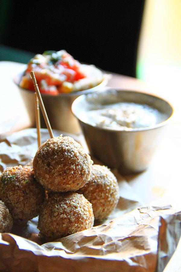 Alcuni falafel tondi uno sull'altro sopra della carta da pane, sullo sfondo una salsa bianca  e un insalatina