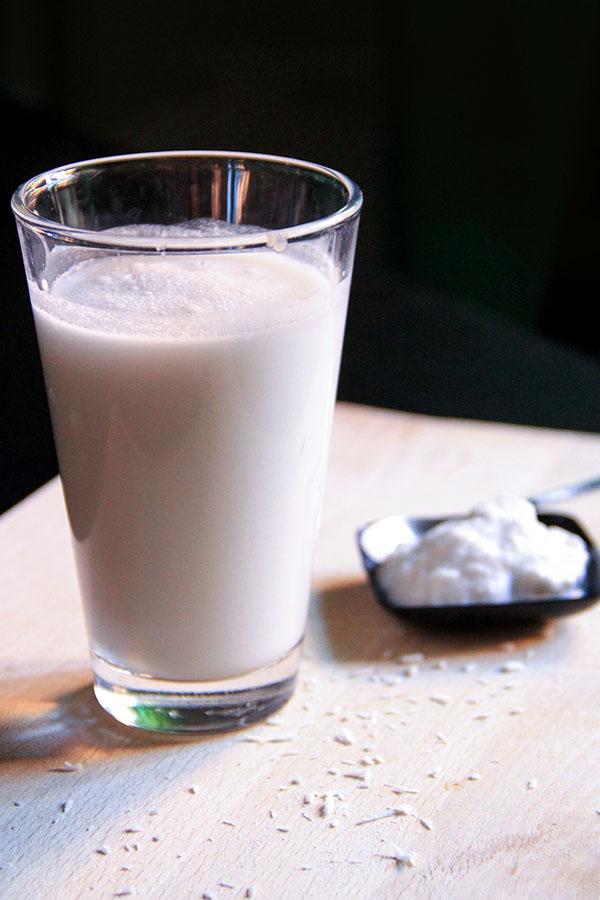 Un bicchiere di Latte di cocco, accanto una ciotolina nera con la parte densa del cocco.
