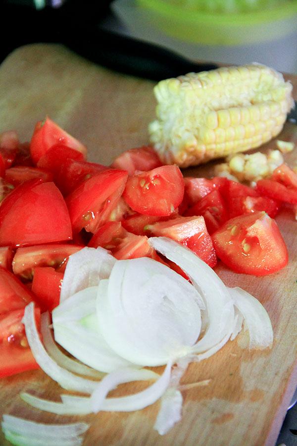 Su un tagliere pomodoro, cipolla e mais