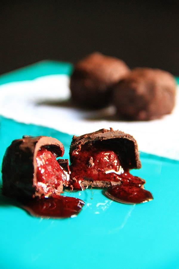 Un cioccolatino a metà in primo piano, con il succo che viene fuori. Sullo sfondo die cioccolatini interi.