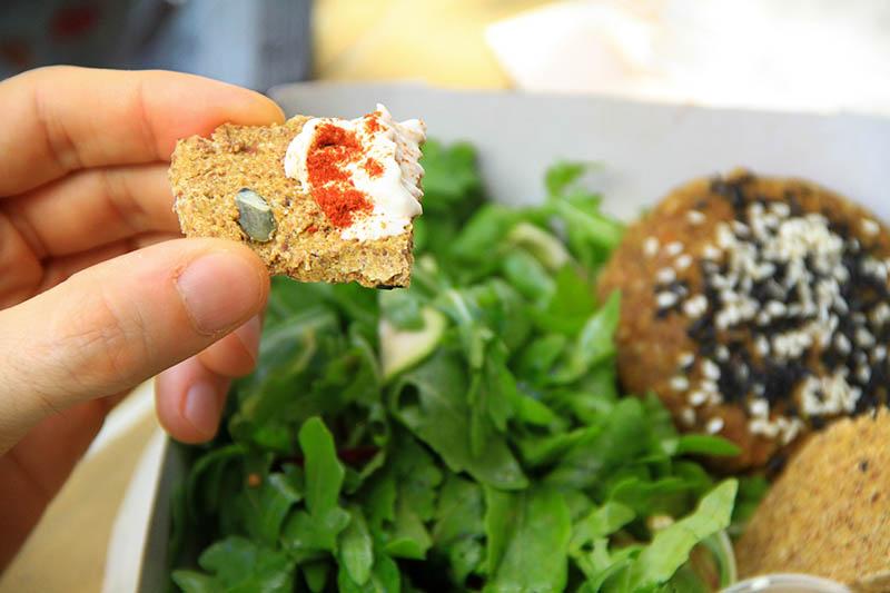 Una mano tiene un pezzetto di Cracker crudista con formaggio