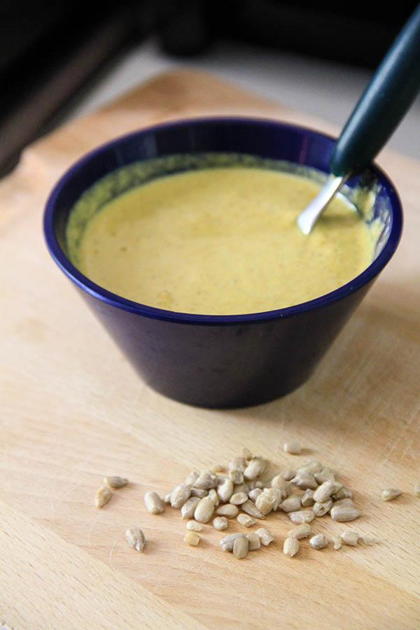 All'interno di una ciotolina blu una salsa al curry. Sul piano di lavoro semi di girasole sparsi.